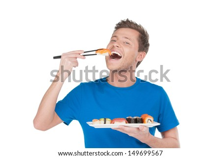 Man enjoying sushi. Handsome young man holding a plate of sushi and eating while standing isolated on white