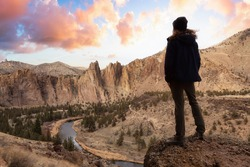 Man enjoying the Beautiful American Mountain Landscape. Dramatic Sunrise Sky Art Render. Taken in Smith Rock, Redmond, Oregon, America. Concept: Adventure, Holiday and Travel