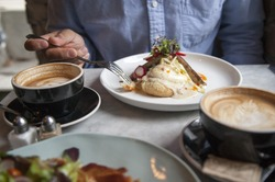 Man enjoys brunch and a latte at a coffee bar and restaurant.