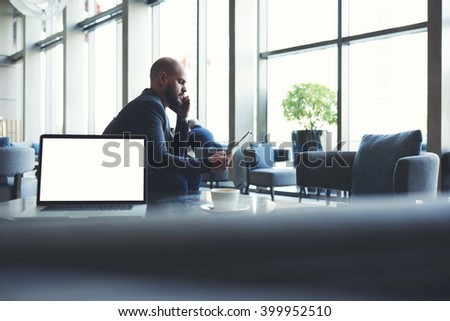 Man entrepreneur is looking on touch pad a bad figure income last month and listening via a mobile phone to the explanation of the subordinate, while is sitting near net-book with copy space screen