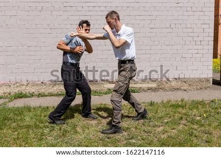 Man evades attacker attack, general plan against a brick wall. Martial arts instructors demonstrate self-defense techniques of Krav Maga