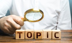 Man examines blocks with topic with a magnifying glass. Conduct research, get an topic explanation. Become an expert, understand the case. Understanding the subject. Assessing value of information