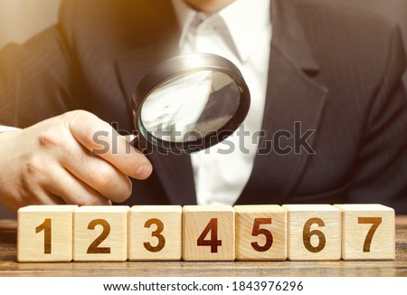 Man examines the numbered blocks with a magnifying glass. Study business plan instructions, contract roadmap. Organization and systematization processes. Education and passing the study course. Stock photo ©