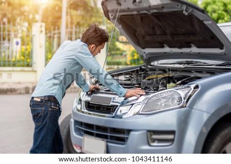 Man examining a broken car on a sunny day #1043411146