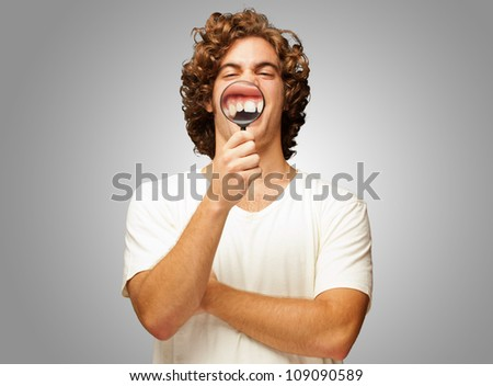 Man Examining His Teeth With Magnifier On Gray Background