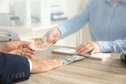 Man exchanging money at cash department window, closeup