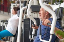Man exercising at gym. Senior athlete doing chest exercises on vertical bench press machine. Strength training benefits for ageing bodies.