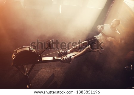Man exercising on rowing machine in a Sunny and hazy health club.