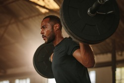 Man exercising with barbell. Male bodybuilder doing weight lifting workout at gym.