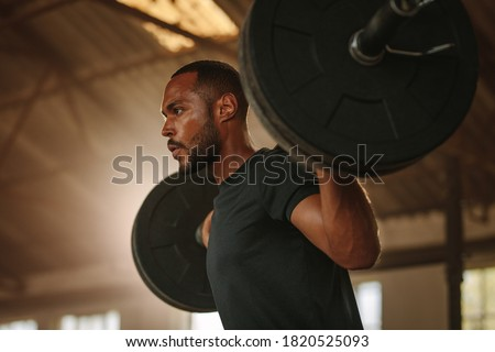 Man exercising with barbell. Male bodybuilder doing weight lifting workout at gym. Сток-фото ©