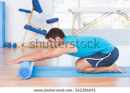 Man exercising with foam roller in fitness studio