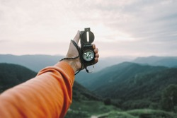Man explorer searching direction with compass in summer mountains, point of view.