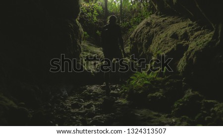 Man exploring cave with lantern on head #1324313507