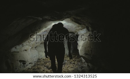 Man exploring cave with lantern on head #1324313525