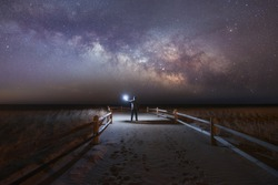 Man exploring the jersey shore under the milky way.
