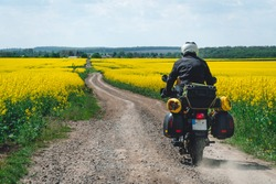 Man extreme sport riding touring enduro motorcycle on dirt. beautiful yellow field of flowers. World adventure rider. Tourist bike. bags and equipment, expedition. discovery. summer day. in action