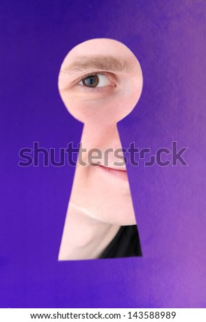 Man eye looking through hole in keyhole, on blue background