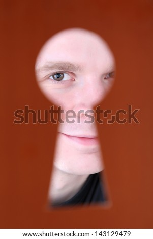 Man eye looking through hole in keyhole, on brown background