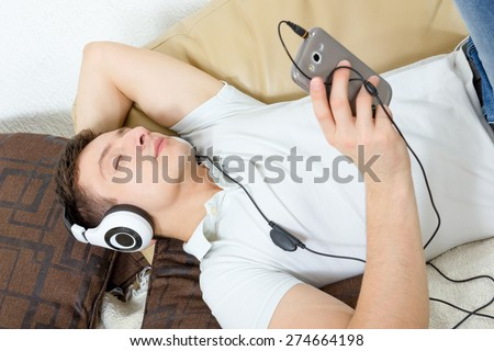 Man fall asleep listening to music over smartphone with headphones , Handsome guy lying on sofa holding mobile phone and listening to music over headset