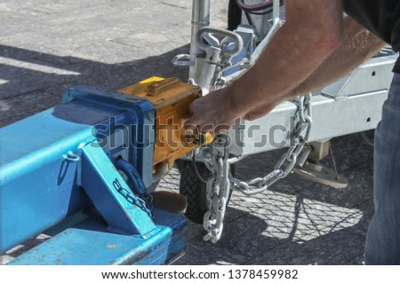 Man fastening a chain onto an industrial hitch on a trailer - close-up #1378459982