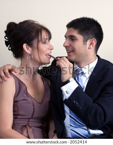man feeding woman chocolate; both are dressed in formal attire as if attending a dinner party or similar event.
