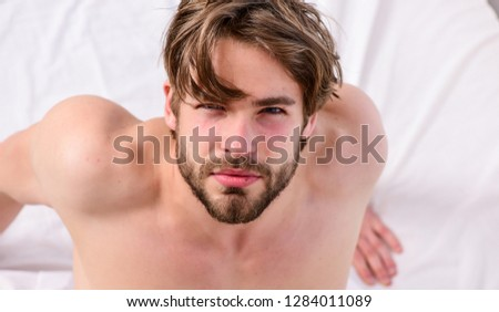 Man feeling back ache in the bed after sleeping. Picture showing young man stretching in bed. Morning