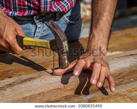 Man feeling his sore hand after having hurt himself while hammering. profession, carpentry, woodwork and people concept.