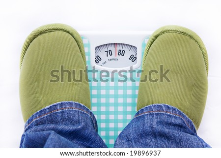 man feet on a bathroom scale showing weight