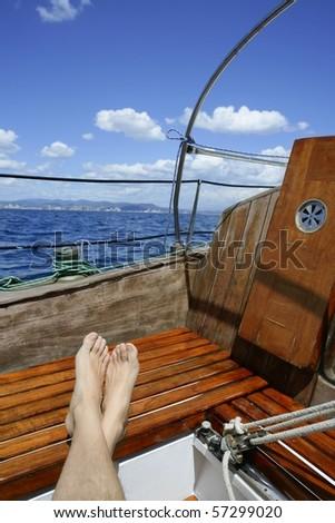 man feet relax on golden wooden old sailboat blue sea summer vacation dream