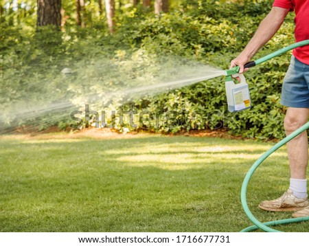Man fertilizing residential backyard lawn with liquid chemical spreader. Landscaper spraying grass lawn with fertilizer, weed killer, and insecticide.