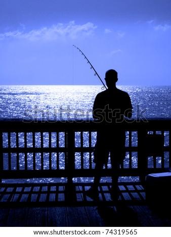 Man ffishing in ocean from a wooden pier