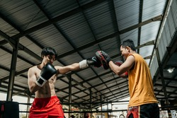 man fighter and coach training together with punching pads at boxing training camp. Guy in boxer glove doing punching workout with her coach