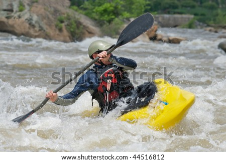 Man fighting the rapids of a river in a kayak.