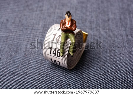 Man figurine and soft measuring tape.  tape measure with metric scale Foto stock ©