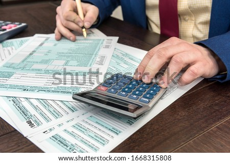 Man fillilng and accounting finance document tax form 1040 with calcualtor. Time for tax Foto stock ©