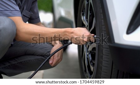 man filling air in the tires of his car (inflating tire)