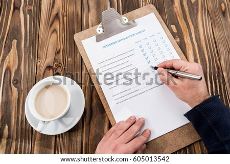 Man Filling In Customer Satisfaction Survey #605013542