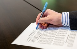 Man filling in Non-Disclosure Agreement NDA - A businessman working on a sheet of paper document