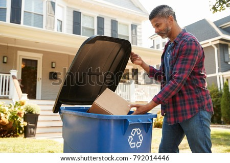Man Filling Recycling Bin On Suburban Street