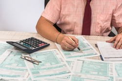 Man filling 1040 tax form at workplace. Performing tax calculations. Close up