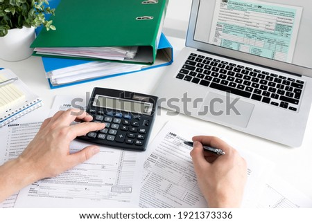 Man filling US tax form. US Individual income tax return. Accountant working with US tax forms