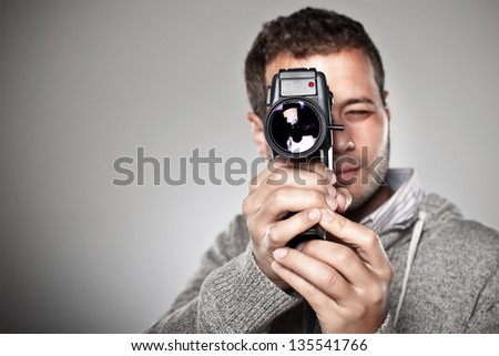 Man filming with a video camera. / Portrait of a normal man with video camera over grey background.