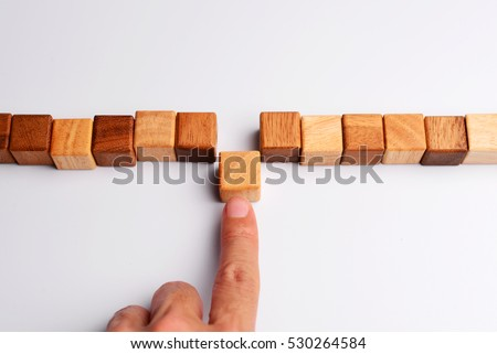 Man finger put last cube wood block to complete and finish wood block in line, symbolizing joining team or making unity teamwork, successful, or completion.    #530264584
