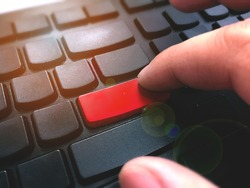 Man finger put the red enter button on computer keyboard