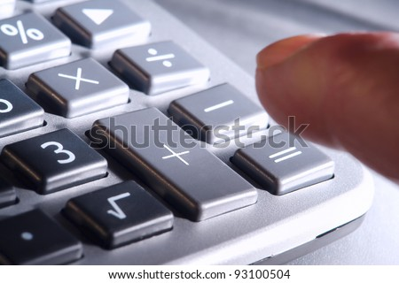Man finger reaching over and ready to punch plus or equal signs keys on a calculator keypad