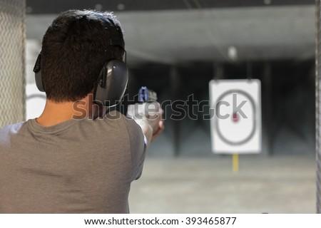 man firing usp pistol at target in indoor fining range