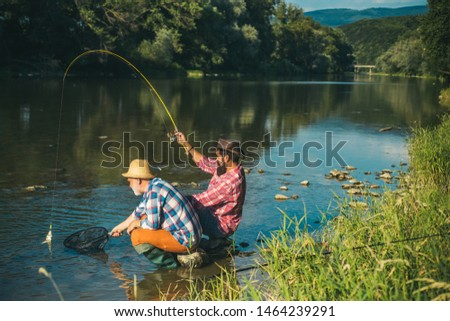 Man fisherman catches a fish. Fly fishing is most renowned as a method for catching trout grayling and salmon #1464239291
