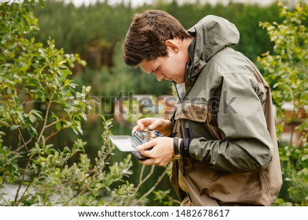 Man fisherman picks box of flies for fly fishing.