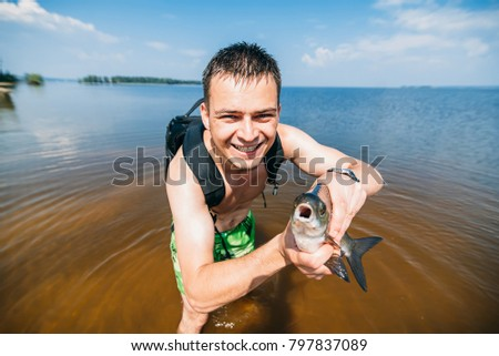 man fisherman with a large fish thrashing at the hands of a happy #797837089