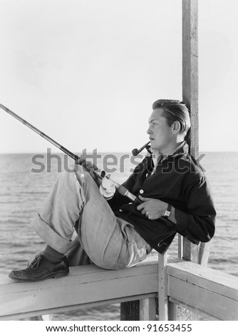 Man fishing and smoking pipe - stock photo